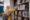 blond female student pulling book library bookshelf